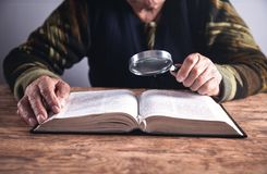 Hand of elderly woman holding magnifier stock photo