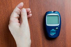 The hand of the elderly woman lies near the device for measureme. Nt of level of sugar in blood Stock Image