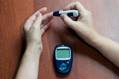 The hand of the elderly woman lies near the device for measureme. Nt of level of sugar in blood Stock Images