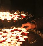 Hand of an elderly woman lights a candle to pray Royalty Free Stock Image