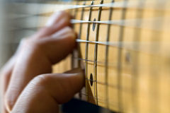 Hand on Electric Guitar Fretboard. Close-up of electric guitar fretboard with hand sliding a chord up the neck Stock Images