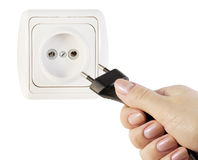 Hand with an electric plug and socket Stock Photos