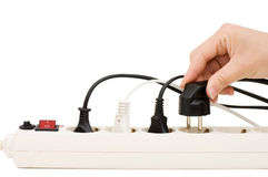 Hand with an electric plug and socket Stock Image
