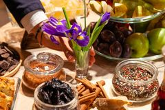 Hand of elegant man with leather bracelet puts flowers, purple irises in glass vase against a buffet table with treats and snacks stock images