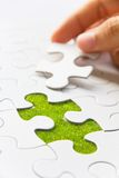 Hand embed missing puzzle piece into place Royalty Free Stock Photos