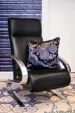 Hand embroidered violet and black pillow on the black chair Stock Photo
