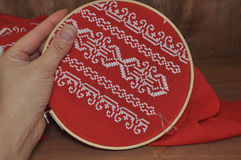 Hand embroidery cross on red cloth with white thread Royalty Free Stock Photo