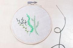 Some hand embroidered green plants. Hand embroidery in a frame with a needle by the side Stock Image