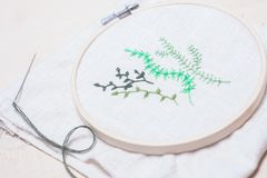 Some hand embroidered green plants. Hand embroidery in a frame with a needle by the side Royalty Free Stock Images