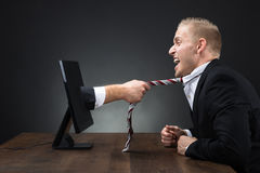 Hand Emerging From Computer Monitor And Pulling Tie Of Executive. Businessman's hand emerging from computer monitor and pulling tie of executive at table Royalty Free Stock Photography