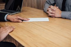 Hand of employer filing final remuneration to employee, letter o. F resignation, resign concept stock image