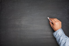 Hand on Empty Blackboard Royalty Free Stock Image