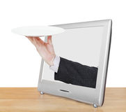 Hand with empty white plate leans out TV screen Stock Photo