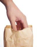 Hand en een document zak royalty-vrije stock afbeelding