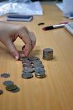Hand en geld op het bureau Stock Foto