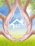 Hand en huis op aardachtergrond Stock Foto