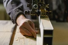 The hand ends the saws on the jigsaw machine. Front view closeup royalty free stock images