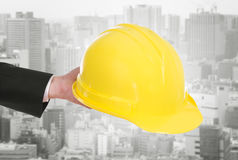 Hand of engineer holding helmet with city background. Hand of engineer holding yellow helmet with city background Royalty Free Stock Images