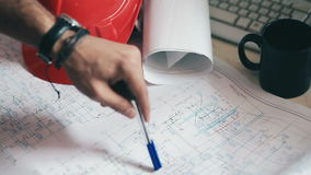 Hand of engineer indicate detail on blueprints. On the table with a cup, a construction helmet and a computer keyboard stock footage
