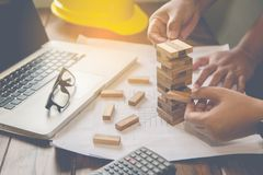 Hand for engineer safety for the game drew to a wooden block fro. M the tower. Concept engineer risks in the job. Requires planning Meditation must be careful in stock photo