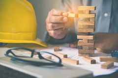Hand for engineer safety for the game drew to a wooden block fro. M the tower. Concept engineer risks in the job. Requires planning Meditation must be careful in stock image