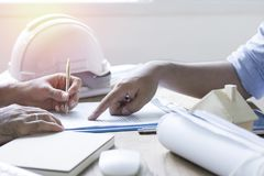 Hand of engineer signing in contract paper and talking with coll Royalty Free Stock Photo
