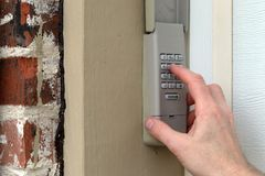 hand entering code on keypad - garage door opener - home security stock photo