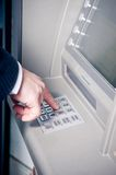 Hand entering pin number on AT Stock Image