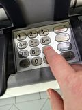 Hand enters a PIN Number into a bancomat royalty free stock photos
