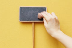 Hand erasing on chalkboard Royalty Free Stock Images