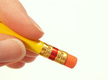 Hand erasing with pencil. Yellow pencil in hand ready to erase stock image