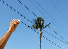 Hand erasing power lines from stock images