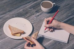 Hand erasing something in a notebook and eat a tasty cheese sandwich. Close up of a plate of sandwich on it and cup of hot cup of. Coffee. Wooden background Stock Photos