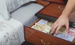 Hand erreicht für das Geld im Nachttisch Stockbild