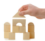 The hand establishes a toy roof on wooden cubes Royalty Free Stock Image