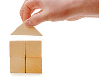 The hand establishes a toy roof on wooden cubes Stock Photo