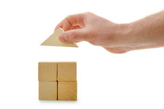 The hand establishes a toy roof on wooden cubes Stock Images
