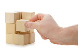 The hand establishes a wooden cube Stock Photography