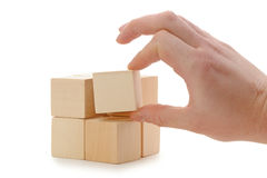 The hand establishes a wooden cube Royalty Free Stock Images