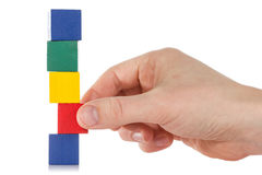 Hand establishes a wooden cube Stock Images