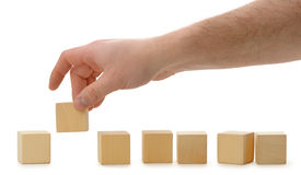 The hand establishes a wooden cube in row Stock Photo
