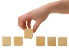 The hand establishes a wooden cube in row Royalty Free Stock Image