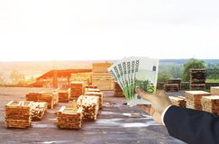Hand with euro money in the background of a warehouse with finished boards, wood, planking royalty free stock photo