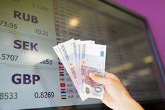 Hand with euro money over currency exchange rates Stock Images