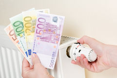 Hand with euro money shows heating costs explosion. Close-up of a heating with hand turning thermostat to full and holding Euro banknotes in other hand Royalty Free Stock Photo