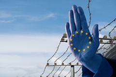 Hand with European flag stops immigration of refugees, blurred b. Order fence in the background, blue sky with copy space royalty free stock image