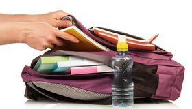 Hand with exercise book and bag Stock Photography