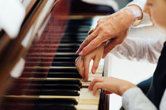 Hand of an experienced pianist helping young students royalty free stock photo