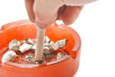 Hand extinguishes his cigarette in an ashtray Royalty Free Stock Images