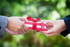 Hand för affärskvinna med julgåvaasken Royaltyfria Bilder